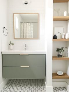 The guest bathroom utilizes a simple Ikea vanity custom painted to the perfect shade of green and features leather hardware from the Australian company Made Measure.