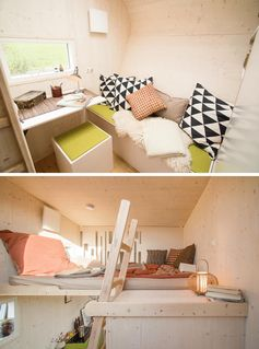 At the end of this modern tiny house is a living room that features a built-in bench with scattered pillows, and a small small desk that's positioned to take in the views from the window. A ladder leads next to the desk leads up to the sleeping loft, that's located above the bathroom. #TinyHouse #ModernTinyHouse #TinyHome #TinyHomeBedroom #LoftedBedroom