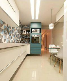 petite cuisine équipée avec meuble en bleu canard et crédence aux motifs géométriques en bleu électrique et taupe, carrelage blanc crème lisse, table carrée n verre avec deux chaises en plastique blanche