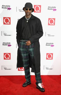 Skepta wears Burberry tartan wool tailored trousers to the Q Awards in London