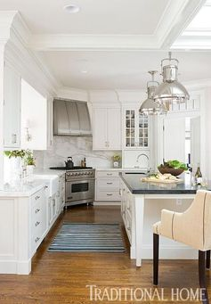 White kitchen cabinets and a stainless steel range helped give this outdated kitchen a fresh, streamlined makeover. - Traditional Home ® / Photo: John Granen / Design: Kelie Grosso