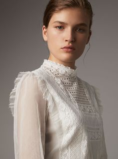 A diaphanous lace and mesh dress with panels of intricate and varied threadwork. Ruffles detail the shoulders and cuffs of the delicate, sheer sleeves.