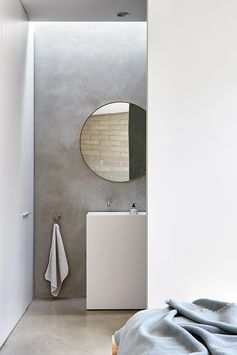 Modern ensuite bathroom with round mirror.