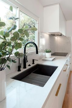 This matte black kitchen sink, which sits below the window, has a matching black faucet and hardware, while the cabinetry hardware adds a luxurious metallic touch.