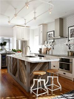 Love the herringbone tile on the wall, echoed in the island. Great contrast, as well, between the slick glossy counter top and the rustic hewn beams.