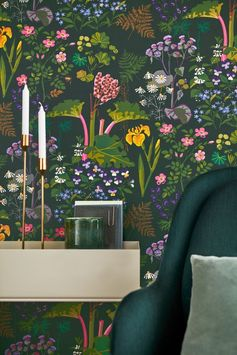 A stunning wallpaper design featuring bright flowers, leaves and rhubarb plants on a dark green background. This design a fabric-like textured effect.