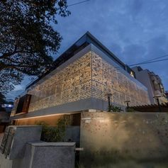 A perforated screen wraps around a modern house.