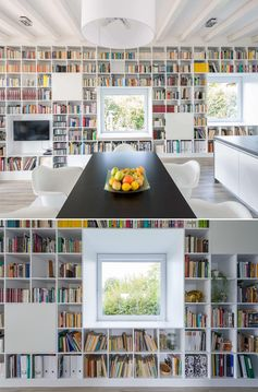 An entire wall is filled with bookshelves and includes window seats.