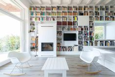 A full wall of white shelving that surrounds a fireplace, television, and windows.