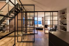 A black framed glass wall with a matching pivoting door.
