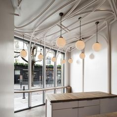In this café, heavy-set mullions are halved and extruded from their frames to form ribbons that curve and fold over the ceiling in a style reminiscent of ornamental plasterwork. #Architecture #InteriorDesign #CafeDesign