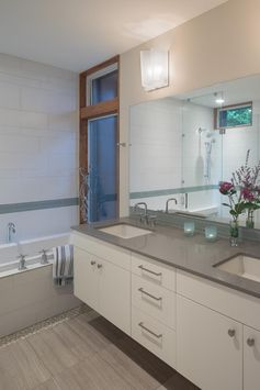 In this modern bathroom, a white vanity with double sinks is topped with a grey countertop, while white tiles adjacent to the bathtub have a strip of color. #BathroomDesign #WhiteBathroom