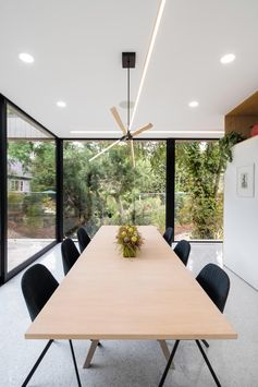 This modern dining room has floor-to-ceiling glass walls look out to the trees, while inside, the wood dining table complements the wood lighting above it. #ModernDiningRoom #GlassWalls