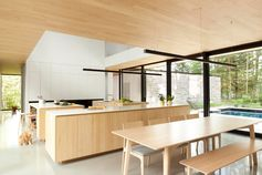 A modern kitchen with three kitchen islands with a light wood base and white countertops.
