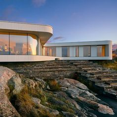 A modern villa with curved glass windows, that sits on a stone base.