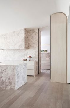 A modern kitchen that uses stone to cover the island, also uses it on the wall, and in the pantry.