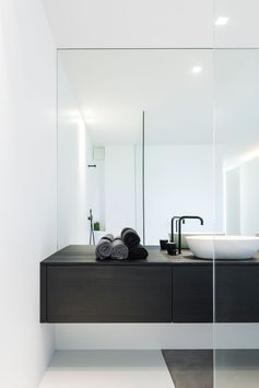 Minimalistisk bad med slette flater, overliggende servant og moderne blandebatteri direkte i benken