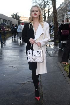 A playful yet sophisticated black and white style: Ava Phillippe in a Valentino Fall 2018 coat and polka dot dress teamed with the new Valentino Garavani VLTN logo Candystud bag.