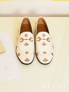A distinctive symbol from the '70s archives, the gold bee is combined with the star motif. Remindful of the House's whimsical narrative, the gold embroidered pattern decorates a Gucci Jordaan loafer in white leather.
