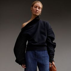 A soft brushed-back jersey sweatshirt with a sculptural panel that extends from the neckline to the sleeve. Exposed seams add textural dimension.