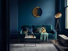 idée de salon bleu petrole avec canapé nuance bleu paon, couverture verte, table minimaliste noire avec plateau blanc, peinture murale bleu marine, tapis gris
