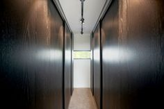 Dark wood walls have doors that slide open to reveal closets. #DarkWood #Closet