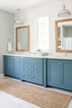 Lake house master bathroom featuring Blustery Sky blue cabinets, white shiplap, and warm wood tones. A pedestal tub and chrome accents complete the look.