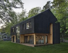 The exterior of this modern house is clad in larch, which is a type of pine tree, and has been charred to give it that burnt look. It also contrasts the recessed wood that's been finished with a natural oil. #BlackHouseSiding #BlackHouse #CharredWoodSiding #ShouSugiBan #BurntWoodSiding
