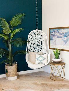 deco salon bleu canard, nuance de pétrole, tapis gris et peau animal, plante verte, balançoire blanche suspendue, coussins decoratifs