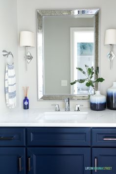 Powder bathroom with Behr Castle Path walls, Benjamin Moore Hale Navy vanity, chrome star sconces, chrome faucet, and ombre blue vases.