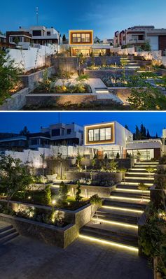 Outdoor lighting highlights the stairs, garden, and sitting areas of this modern house.