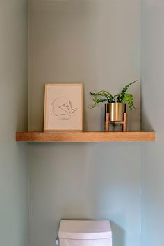 A small powder room with a single wood shelf that showcases art and a plant.