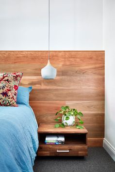 This modern master bedroom has a wood headboard, floating wood bedside tables, and modern pendant lights. #ModernBedroom #BedroomDesign