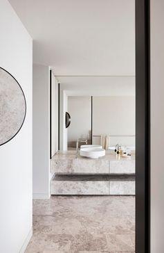 A modern bathroom with limestone vanity and floors.