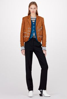 Louis Vuitton Cruise 2018 - Look 2 This look combines one of the season's statement leather pieces with straight pants to create an emblematic silhouette. The jacket's stud embroidery is a seasonal motif, while the pants' contrasting bands are a Nicolas Ghesquière signature. A suede gilet and stylish knitted top complete the effect.
