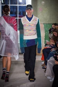 A blue Fair Isle patchwork sweater knitted in Wales from mouliné yarn is worn under a white wool V-neck tank top. Wide-leg trousers are added with cotton socks and yellow kiltie loafers for the completed look.