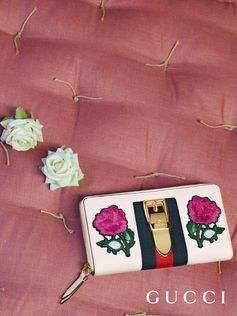Embroidered flower appliqués embellish the new Sylvie zip around wallet from Gucci Cruise 2018 by Alessandro Michele.