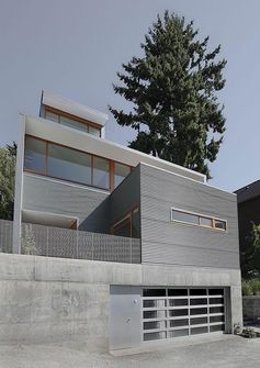 A modern house with corrugated metal siding, concrete foundation, and wood window frames.
