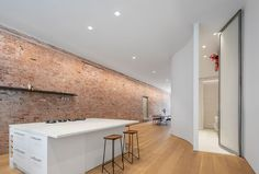 The old brick wall runs the full length of this modern loft, while on the opposite wall, a curved wall hides the bathroom behind a 13 foot tall custom sand-blasted pivot door. #ModernLoft #LoftIdeas #Apartment #BrickWall