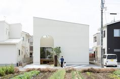 12 Minimalist Modern House Exteriors From Around The World | An all white exterior wall provides privacy for the home and makes the exterior of the house look simple and modern with the angled roof and arched entrance.