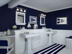 une belle salle de bain en bleu foncé avec un voilier blanc décoratif