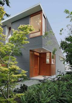 A modern house with corrugated metal siding and a wood front door and window frames.