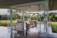This modern office is surrounded by glass to allow for uninterrupted views of the garden. #GlassWalls #OfficeDesign