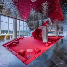 A sunken built-in red seating area in an office building.