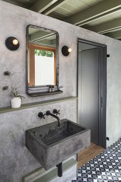 The new casita bathroom features a custom concrete sink, plaster walls, and custom concrete tile.