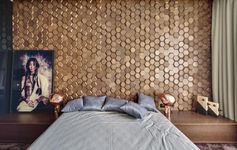 This modern bedroom has an eye-catching accent wall made from 3-dimensional hexagonal wood tiles in a honeycomb pattern. #WoodTiles #WoodAccentWall #3DAccentWall #BedroomDesign #InteriorDesign