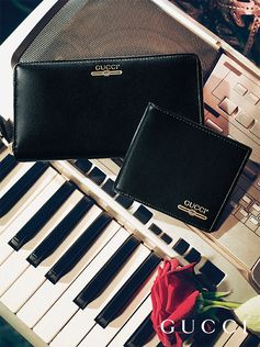 A retro style Gucci logo details men's black leather wallets from Gucci Gift, designed by Alessandro Michele.