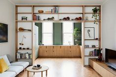 This modern living room has custom built wood shelves that wrap around the open doorway to the kitchen, while cork flooring flows between both areas. #Shelving #CorkFlooring #LivingRoom #Kitchen