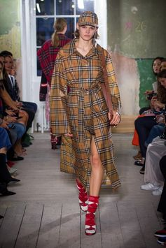 A tactile waterproof coat in Vintage check with equestrian-influenced buckled straps with The Pocket Satchel in tan. Vibrant red tartan high-heel sandals and knitted socks complete the look.
