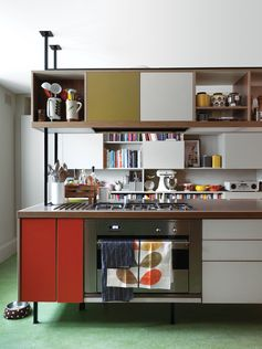 """Kitchen Confidential   Kiely and architect Maxim Laroussi designed the kitchen unit. """"I originally didn't want an island, but I liked what we did because it feels like a piece of furniture. It's cozy to cook around,"""" Kiely says. Panels of orange and olive Formica accent the 1950s-inspired piece, which houses a cooktop by Smeg. A checkerboard of closed cabinets and open shelves offers storage against the far wall for Kiely's collection of dishes, knickknacks, cookbooks, and small appliances, ..."""